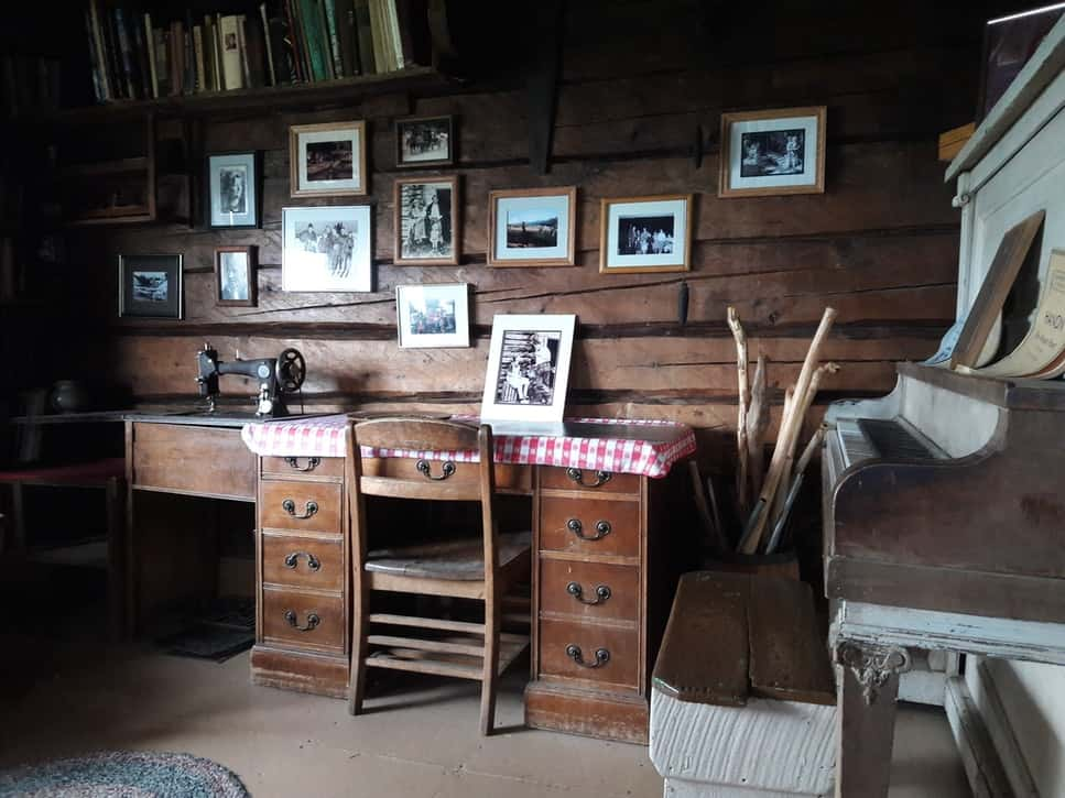 Wooden desk with photos behind and piano in a log cabin