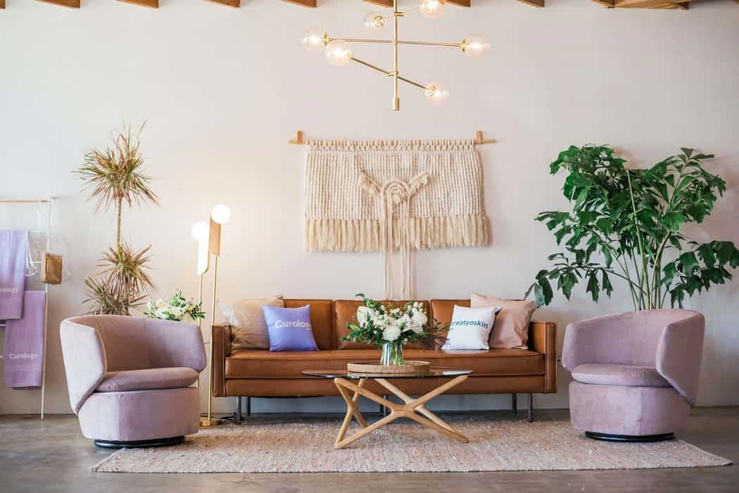 sofa in the middle of two purple round chairs with a coffee table, plants and lights