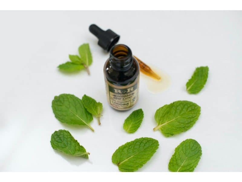 natural oil with leaves around a glass bottle with pipette