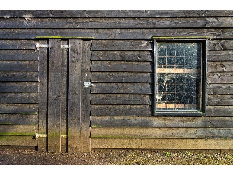 wooden shed with boarded up doors and grated window