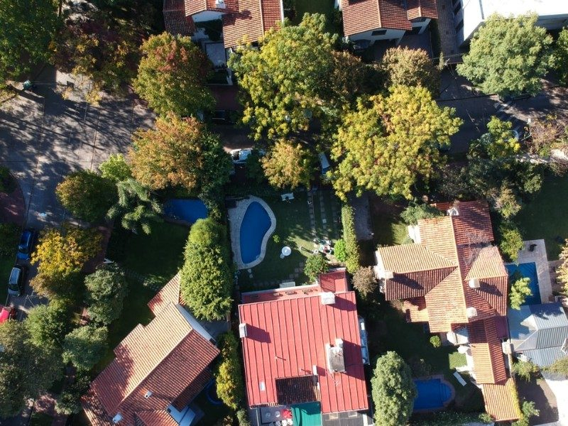 aerial views of houses, trees, and a pool