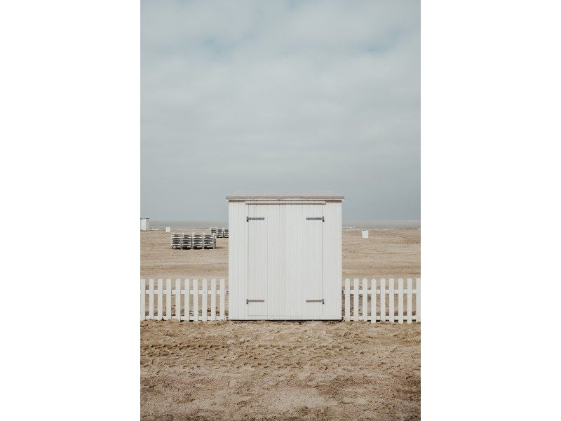 wooden shed on a beach against a small white picket fence