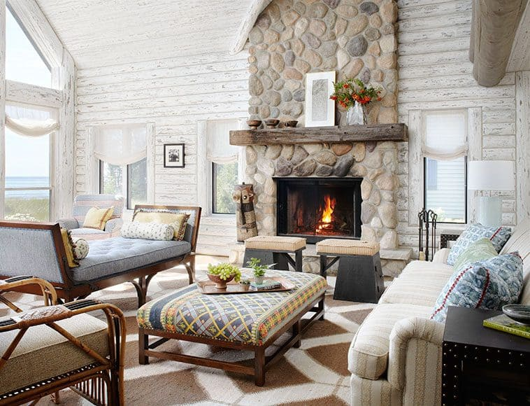 Shabby Chic Log Cabin Interior with cream coloured sofas an ottoman in front of a brick chimney fire