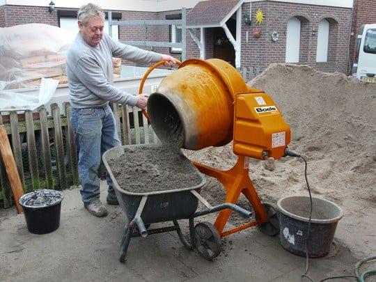 Man stood at cement mixer tipping it into wheelbarrow
