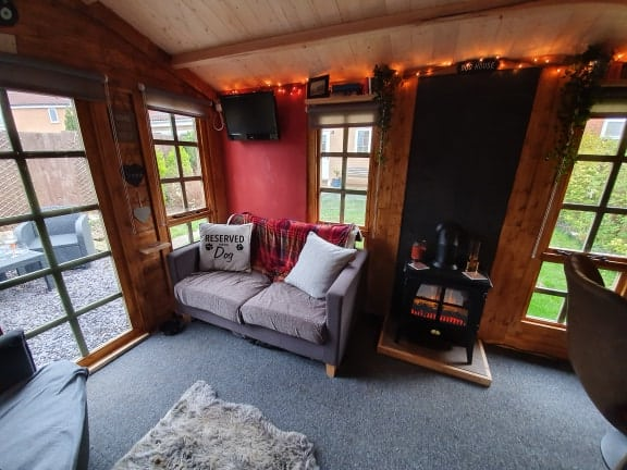 log cabin summerhouse interior with sofas and a wood burner