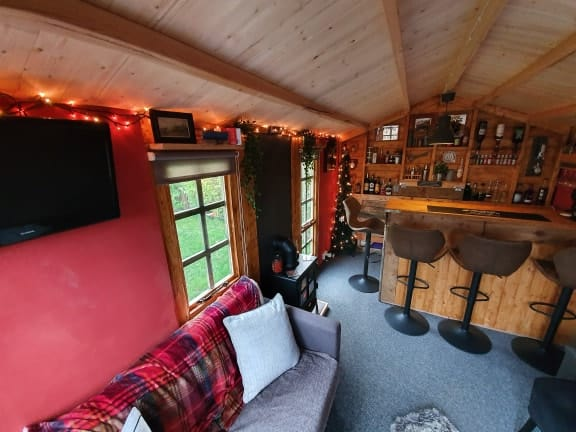BillyOh log cabin summerhouse interior with Nightjar bar and sofa and stools