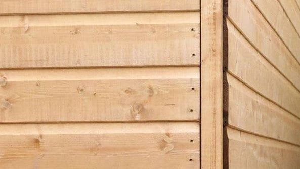 corner of a shiplap tongue and groove timber shed with nails near corner join