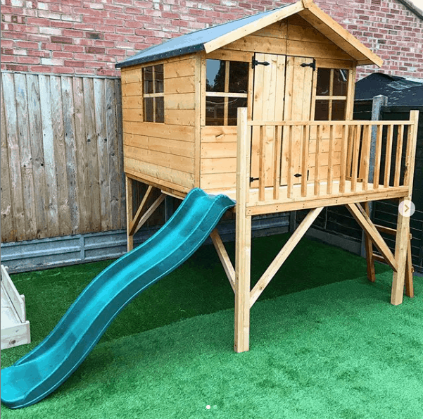 wooden tower playhouse with apex roof and slide and veranda on astro turf