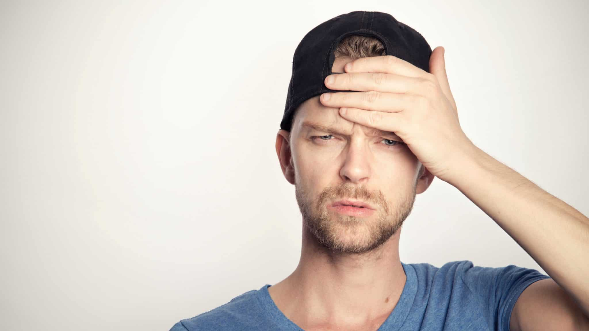 man wearing a backwards baseball cap looking confused with his hand to his head