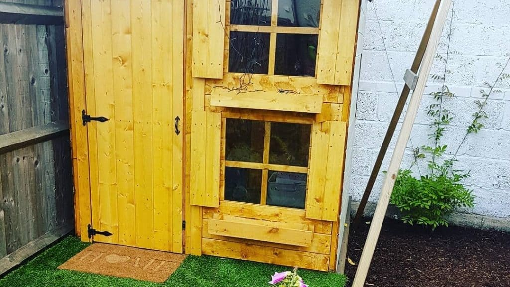 two storey wooden playhouse with stacked windows on astroturf
