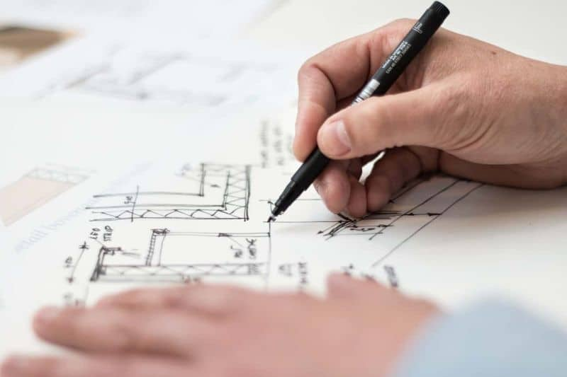 hands drawing architectural plans