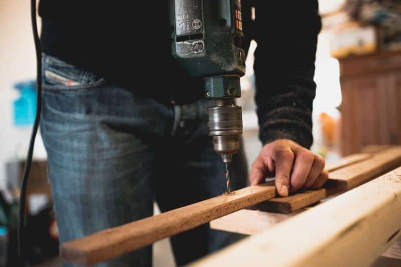 man wearing jeans drilling a hole in thin length of timber