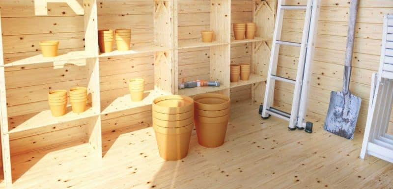Shed interior with shelving, plant pots, ladder, and spade